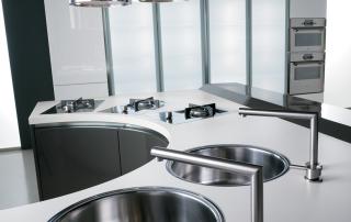 Cucina moderna_Maxima Round_dettaglio top unicolor bianco e lavelli singoli a bacinella incassati. Fuochi a filo top. Cappe a cilindro in acciaio inox