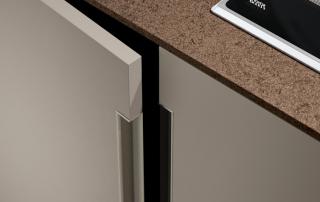 Cucina moderna_Lounge.01_dettaglio maniglia verticale in alluminio finitura titanio. Si innesta nell'anta da 22 mm creando un particolare di forte personalizzazione; top da 12 mm in light quarz Amazon tono su tono con il laccato platino (A08) dell'anta