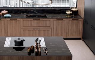 Cucina contemporanea_Marilyn 45.02_dettaglio Laminam Noir Desir per top e fianchi di finitura isola, con lavello integrato per basi cucina. Il tavolo con top a forte spessore in legno sembra sospeso nel vuoto, una lastra in vetro temperato lo sostiene, conferendo una sensazione di leggerezza alla parte terminale dell'isola