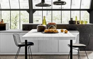 Cucina moderna_Pepper.02_dettaglio tavolo a forte spessore (dim 180x80x6 cm) in appoggio all'isola, piano a doghe in legno massello con incisioni a sequenza irregolare, gambe in metallo con parte terminale in fusione di acciaio, finitura bronzo