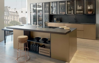 Modern Kitchens_Linea HD_version with pan drawers dropping at 2cm from the floor. Multifunctional island with a brand-new open compartment under the snack top. Linear wall. Side units and hanging showcase columns with glass frame and completely transparent ending side units. Tall cabinet with variously equippable pocket doors. Finishes: matt metal lacquered with scratched gold look, eucalyptus wood veneered, black frame door with smoked V5 glass, worktop and backsplash in Laminam black oxyd