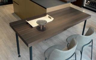 Cucina moderna_Linea HD_dettaglio isola multifunzionale con vano giorno sotto il piano snack. Finitura laccato opaco metallo effetto graffiato oro, essenza di eucalipto, ante con vetro fumè e telaio nero, top e fondale in laminam ossido nero